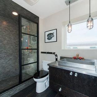 カルガリーのインダストリアルスタイルのおしゃれなバスルーム (浴槽なし) (フラットパネル扉のキャビネット、アルコーブ型シャワー、分離型トイレ、モザイクタイル、ベージュの壁、濃色無垢フローリング、ベッセル式洗面器、ステンレスの洗面台、黒いキャビネット、グレーのタイル、開き戸のシャワー) の写真