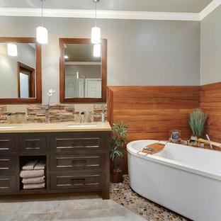 Esempio di una stanza da bagno minimal con piastrelle in gres porcellanato, pavimento con piastrelle di ciottoli e vasca freestanding