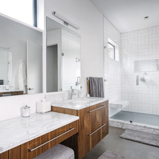 Design ideas for a medium sized contemporary ensuite bathroom in Austin with flat-panel cabinets, an alcove shower, a two-piece toilet, white tiles, white walls, concrete flooring, a submerged sink, a hinged door, medium wood cabinets, stone tiles, marble worktops, grey floors, an alcove bath, grey worktops, a wall niche and a shower bench.