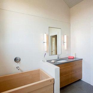 Idee per una stanza da bagno padronale boho chic di medie dimensioni con ante lisce, ante in legno scuro, vasca giapponese, doccia aperta, pareti grigie, WC a due pezzi, pavimento in ardesia, lavabo sottopiano e top in superficie solida
