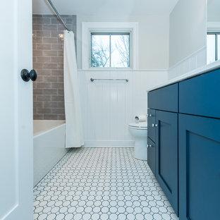 Modelo de cuarto de baño infantil, contemporáneo, de tamaño medio, con armarios con paneles empotrados, puertas de armario azules, bañera empotrada, combinación de ducha y bañera, sanitario de dos piezas, baldosas y/o azulejos grises, baldosas y/o azulejos de cemento, parades naranjas, suelo con mosaicos de baldosas, lavabo bajoencimera, encimera de cuarzo compacto, suelo blanco y ducha con cortina