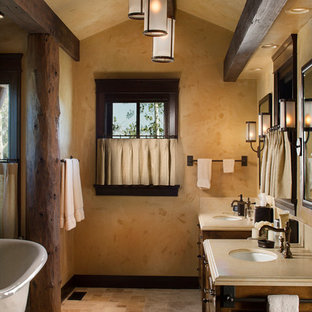Example of a mid-sized mountain style master beige tile and ceramic tile beige floor and ceramic floor bathroom design in Other with an undermount sink, dark wood cabinets, shaker cabinets, beige walls and soapstone countertops