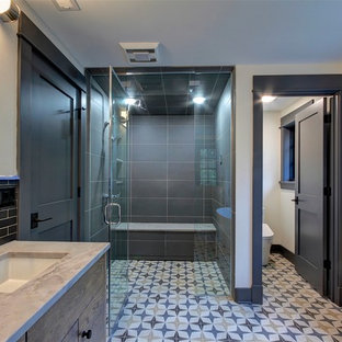 Transitional master black tile cement tile floor and multicolored floor walk-in shower photo in Cleveland with flat-panel cabinets, a two-piece toilet, beige walls, an undermount sink, a hinged shower door and beige countertops