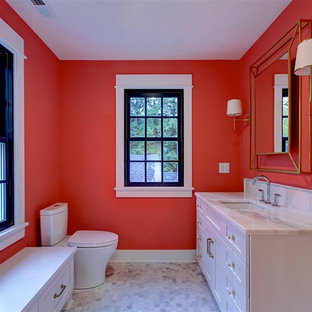 Example of a transitional 3/4 gray floor bathroom design in Cleveland with recessed-panel cabinets, white cabinets, a two-piece toilet, orange walls, an undermount sink and white countertops
