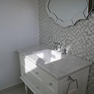 Imagen de cuarto de baño bohemio, pequeño, con armarios tipo mueble, puertas de armario blancas, baldosas y/o azulejos grises, baldosas y/o azulejos con efecto espejo, ducha esquinera, sanitario de una pieza, lavabo bajoencimera, paredes grises y suelo de baldosas de porcelana