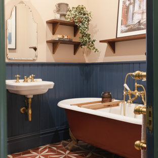 Immagine di una stanza da bagno chic con vasca con piedi a zampa di leone, pareti multicolore, pavimento in cementine, lavabo sospeso e pavimento rosso