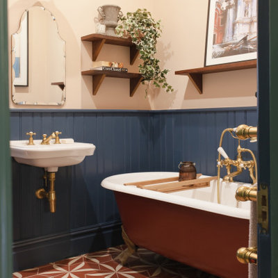 Inspiration for a transitional cement tile floor and red floor claw-foot bathtub remodel in London with multicolored walls and a wall-mount sink