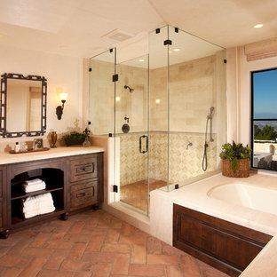 Exemple d'une salle de bain principale méditerranéenne avec des portes de placard en bois sombre, une baignoire encastrée, une douche d'angle, un carrelage beige, un mur beige, un sol en carreau de terre cuite, un placard avec porte à panneau surélevé et un sol beige.