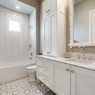 Imagen de cuarto de baño infantil, retro, de tamaño medio, con armarios estilo shaker, puertas de armario blancas, bañera esquinera, ducha empotrada, sanitario de una pieza, baldosas y/o azulejos grises, baldosas y/o azulejos de porcelana, paredes grises, suelo de baldosas de porcelana, lavabo bajoencimera, encimera de cuarzo compacto, suelo gris, ducha con cortina y encimeras blancas