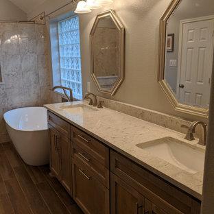 На фото: главная ванная комната среднего размера в классическом стиле с фасадами в стиле шейкер, фасадами цвета дерева среднего тона, отдельно стоящей ванной, открытым душем, унитазом-моноблоком, бежевой плиткой, мраморной плиткой, серыми стенами, полом из плитки под дерево, врезной раковиной, столешницей из искусственного кварца, коричневым полом, открытым душем, бежевой столешницей, сиденьем для душа, тумбой под две раковины и встроенной тумбой с