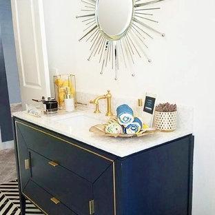 Immagine di una stanza da bagno padronale mediterranea di medie dimensioni con ante lisce, ante blu, pavimento con piastrelle in ceramica, top in onice e pavimento nero