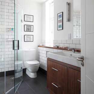 Small contemporary kids bathroom in London with an integrated sink, flat-panel cabinets, dark wood cabinets, a corner shower, white tile, white walls, grey floor, a one-piece toilet, ceramic tile, slate floors, wood benchtops, a hinged shower door, brown benchtops, a double vanity and a built-in vanity.