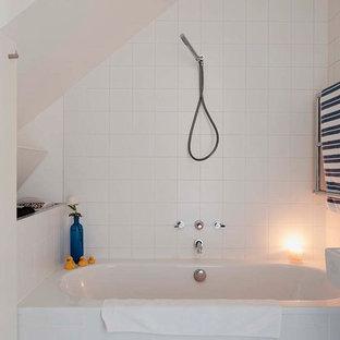 Modelo de cuarto de baño infantil, contemporáneo, pequeño, con bañera encastrada, ducha a ras de suelo, sanitario de pared, baldosas y/o azulejos blancos, paredes blancas, suelo de terrazo, lavabo suspendido, suelo blanco y ducha con puerta con bisagras
