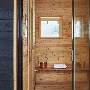 Imagen de sauna escandinava con paredes marrones, suelo de madera en tonos medios y suelo marrón