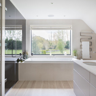 Design ideas for a large contemporary bathroom in London with flat-panel cabinets, white cabinets, a built-in bath, beige walls, a submerged sink, beige floors and beige worktops.