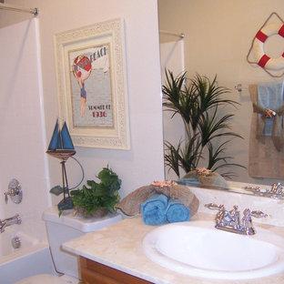 Imagen de cuarto de baño infantil, exótico, de tamaño medio, con lavabo encastrado, puertas de armario de madera oscura, encimera de granito, bañera encastrada, ducha empotrada, sanitario de una pieza y paredes beige