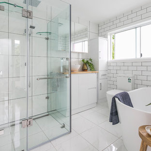 Design ideas for a contemporary master bathroom in Hobart with flat-panel cabinets, white cabinets, a freestanding tub, a corner shower, a two-piece toilet, white tile, white walls, a vessel sink, wood benchtops, white floor and a hinged shower door.