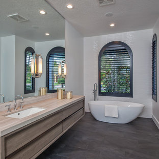 Photo of a medium sized contemporary ensuite bathroom in Miami with flat-panel cabinets, medium wood cabinets, a freestanding bath, white tiles, white walls, a submerged sink, grey floors, an alcove shower, ceramic tiles, slate flooring, engineered stone worktops and a hinged door.