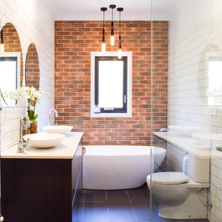 Mid-sized transitional master bathroom in Melbourne with flat-panel cabinets, dark wood cabinets, a freestanding tub, white tile, a vessel sink, engineered quartz benchtops, grey floor, a hinged shower door, a corner shower, a two-piece toilet, subway tile and white walls.