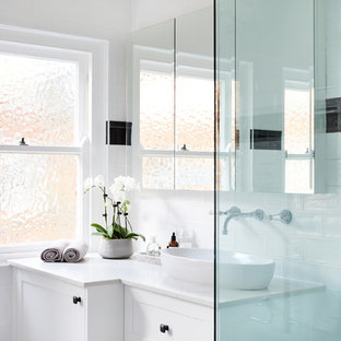 This is an example of a traditional bathroom in Sydney with recessed-panel cabinets, white cabinets, a corner shower, black tile, white tile, white walls, a vessel sink and white benchtops.