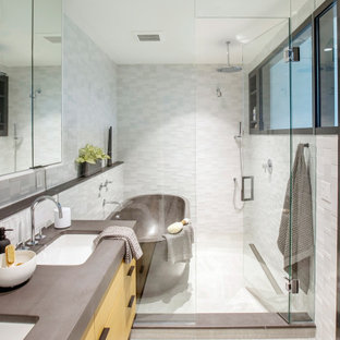 This is an example of a mid-sized contemporary master wet room bathroom in Vancouver with flat-panel cabinets, medium wood cabinets, a freestanding tub, white tile, mosaic tile, porcelain floors, an undermount sink, concrete benchtops, grey floor, a hinged shower door, grey benchtops and a double vanity.