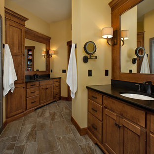 Small elegant master multicolored tile and stone slab slate floor bathroom photo in Grand Rapids with an undermount sink, recessed-panel cabinets, medium tone wood cabinets, engineered quartz countertops, a one-piece toilet and yellow walls