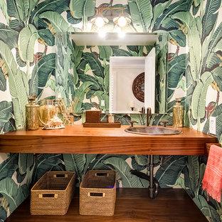 Großes Kolonialstil Duschbad mit Einbauwaschbecken, hellbraunen Holzschränken, Waschtisch aus Holz, Toilette mit Aufsatzspülkasten, grüner Wandfarbe, braunem Holzboden, offenen Schränken und brauner Waschtischplatte in San Diego