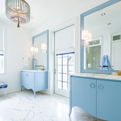 Example of a beach style white floor bathroom design in Miami with flat-panel cabinets, blue cabinets, white walls, an undermount sink and white countertops