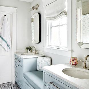 Ejemplo de cuarto de baño costero con armarios con paneles empotrados, puertas de armario azules, paredes grises, suelo con mosaicos de baldosas, lavabo bajoencimera, suelo multicolor y encimeras blancas