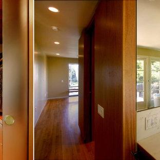 Foto de sauna minimalista, pequeña, con armarios con paneles lisos, puertas de armario de madera oscura, bañera exenta, sanitario de una pieza, baldosas y/o azulejos marrones, losas de piedra, paredes verdes, suelo de madera clara, lavabo bajoencimera y encimera de piedra caliza