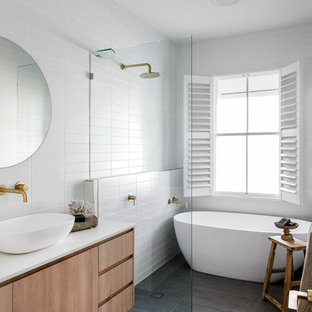 Beach style 3/4 bathroom in Brisbane with flat-panel cabinets, medium wood cabinets, a freestanding tub, a curbless shower, white tile, white walls, a vessel sink, grey floor, an open shower and white benchtops.