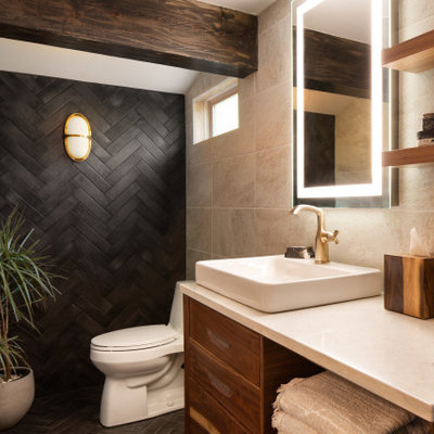 Example of a small trendy master beige tile and ceramic tile ceramic tile, black floor, single-sink and exposed beam bathroom design in Kansas City with flat-panel cabinets, medium tone wood cabinets, a one-piece toilet, black walls, a vessel sink, quartzite countertops, white countertops and a floating vanity