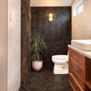 カンザスシティの小さいコンテンポラリースタイルのおしゃれなマスターバスルーム (フラットパネル扉のキャビネット、中間色木目調キャビネット、置き型浴槽、オープン型シャワー、一体型トイレ、ベージュのタイル、セラミックタイル、黒い壁、セラミックタイルの床、ベッセル式洗面器、珪岩の洗面台、黒い床、オープンシャワー、白い洗面カウンター、洗面台1つ、フローティング洗面台、表し梁) の写真