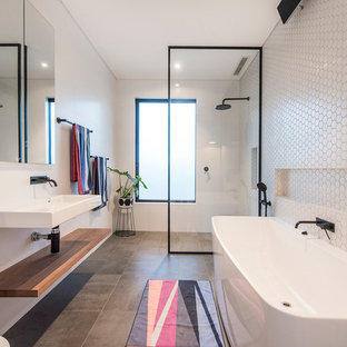 This is an example of a contemporary master bathroom in Perth with flat-panel cabinets, light wood cabinets, a one-piece toilet, white tile, porcelain tile, white walls, travertine floors, a wall-mount sink, grey floor, an open shower and an open shower.