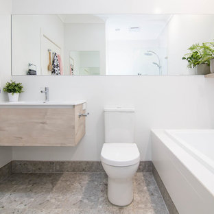 Contemporary bathroom in Adelaide with flat-panel cabinets, light wood cabinets, a drop-in tub, white walls, a console sink and grey floor.
