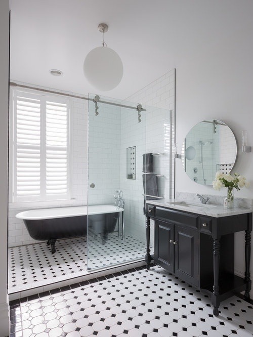 example of an ornate master glass tile ceramic floor bathroom design in auckland with black cabinets