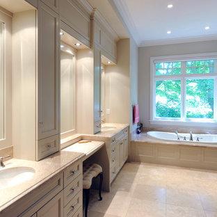 Klassisk inredning av ett stort en-suite badrum, med luckor med infälld panel, beige skåp, ett badkar i en alkov, beige väggar, klinkergolv i keramik, ett undermonterad handfat och marmorbänkskiva