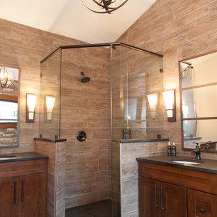 Imagen de cuarto de baño principal, rural, de tamaño medio, con lavabo bajoencimera, armarios estilo shaker, puertas de armario de madera en tonos medios, encimera de granito, ducha esquinera, baldosas y/o azulejos marrones, baldosas y/o azulejos de porcelana y suelo de pizarra