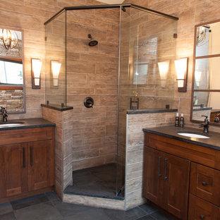Idées déco pour une grand salle de bain principale montagne avec un placard à porte shaker, des portes de placard en bois sombre, une douche d'angle, un carrelage marron, des carreaux de porcelaine, un sol en ardoise, un lavabo encastré, un plan de toilette en stéatite, un sol gris et une cabine de douche à porte battante.