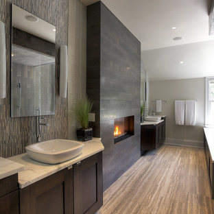 Foto de cuarto de baño actual, grande, con lavabo sobreencimera, armarios estilo shaker, puertas de armario de madera en tonos medios, bañera encastrada sin remate, baldosas y/o azulejos grises, paredes blancas y suelo de madera oscura