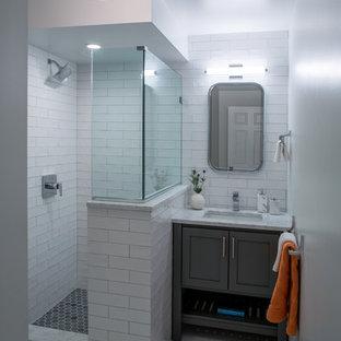 ニューヨークの中サイズのコンテンポラリースタイルのおしゃれなバスルーム (浴槽なし) (シェーカースタイル扉のキャビネット、グレーのキャビネット、コーナー設置型シャワー、白いタイル、サブウェイタイル、グレーの壁、玉石タイル、アンダーカウンター洗面器、珪岩の洗面台、グレーの床、開き戸のシャワー) の写真