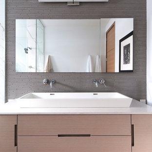 Idee per una stanza da bagno minimalista con lavabo rettangolare, ante lisce, ante in legno chiaro, piastrelle grigie e piastrelle di vetro