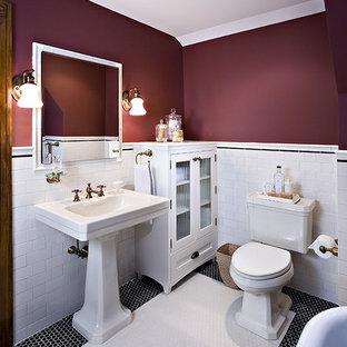 Kleines Klassisches Badezimmer En Suite mit Sockelwaschbecken, weißen Schränken, Duschnische, Wandtoilette mit Spülkasten, weißen Fliesen, Keramikfliesen, roter Wandfarbe, Keramikboden, Glasfronten, weißem Boden und Falttür-Duschabtrennung in Detroit
