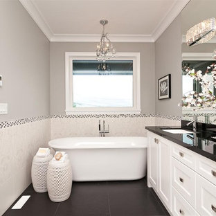 Trendy White Tile Black Floor Freestanding Bathtub Photo In Vancouver With An Undermount Sink Recessed