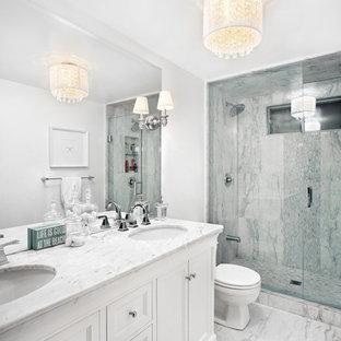 Idéer för ett mellanstort klassiskt en-suite badrum, med ett undermonterad handfat, vita skåp, marmorbänkskiva, vit kakel, stenkakel, vita väggar, marmorgolv, en dusch i en alkov och luckor med infälld panel