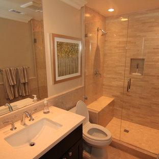 オレンジカウンティのトランジショナルスタイルのおしゃれなバスルーム (浴槽なし) (アンダーカウンター洗面器、シェーカースタイル扉のキャビネット、濃色木目調キャビネット、クオーツストーンの洗面台、オープン型シャワー、一体型トイレ、ベージュのタイル、石タイル、ベージュの壁、磁器タイルの床) の写真