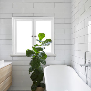 Design ideas for a contemporary 3/4 bathroom in Perth with flat-panel cabinets, light wood cabinets, a freestanding tub, white tile and white walls.
