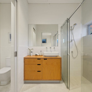 Midcentury 3/4 bathroom in Perth with flat-panel cabinets, light wood cabinets, a curbless shower, a one-piece toilet, white tile, white walls, a vessel sink, wood benchtops, beige floor, a sliding shower screen, an enclosed toilet, a single vanity and a floating vanity.