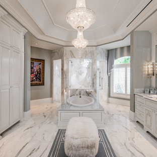 Tuscan master white tile and marble tile marble floor and white floor bathroom photo in Miami with furniture-like cabinets, white cabinets, gray walls and an undermount sink