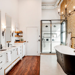 Example of an urban master gray tile and ceramic tile laminate floor and brown floor bathroom design in Other with flat-panel cabinets, distressed cabinets, white walls, an undermount sink, quartzite countertops, a hinged shower door and white countertops